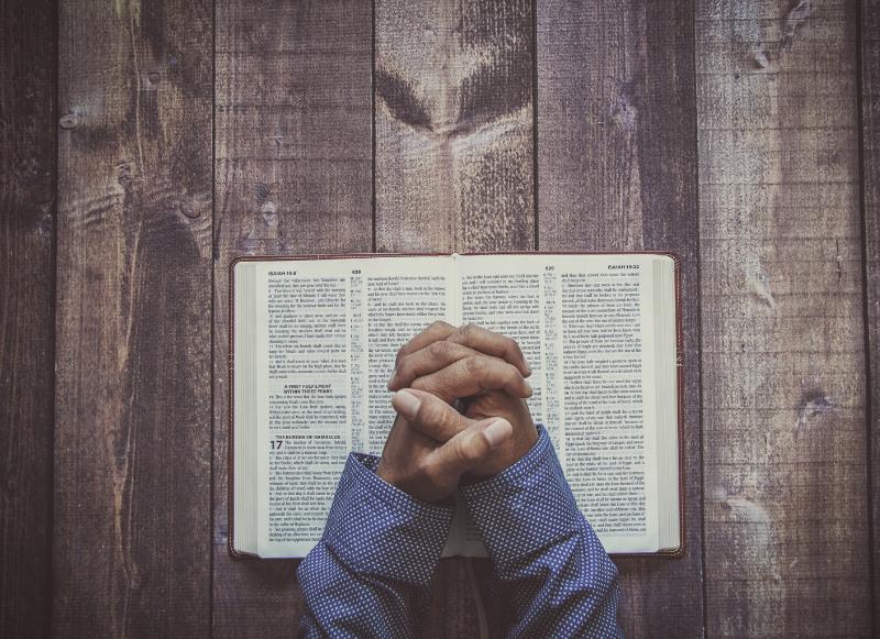 Praying hands above a bible